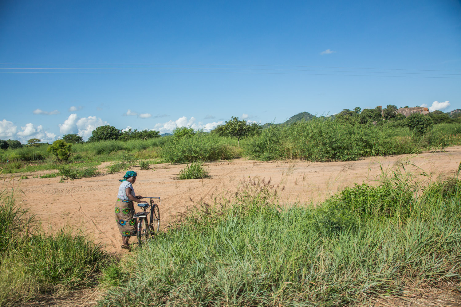 Malawian woman pushes bicycle across desert-like land