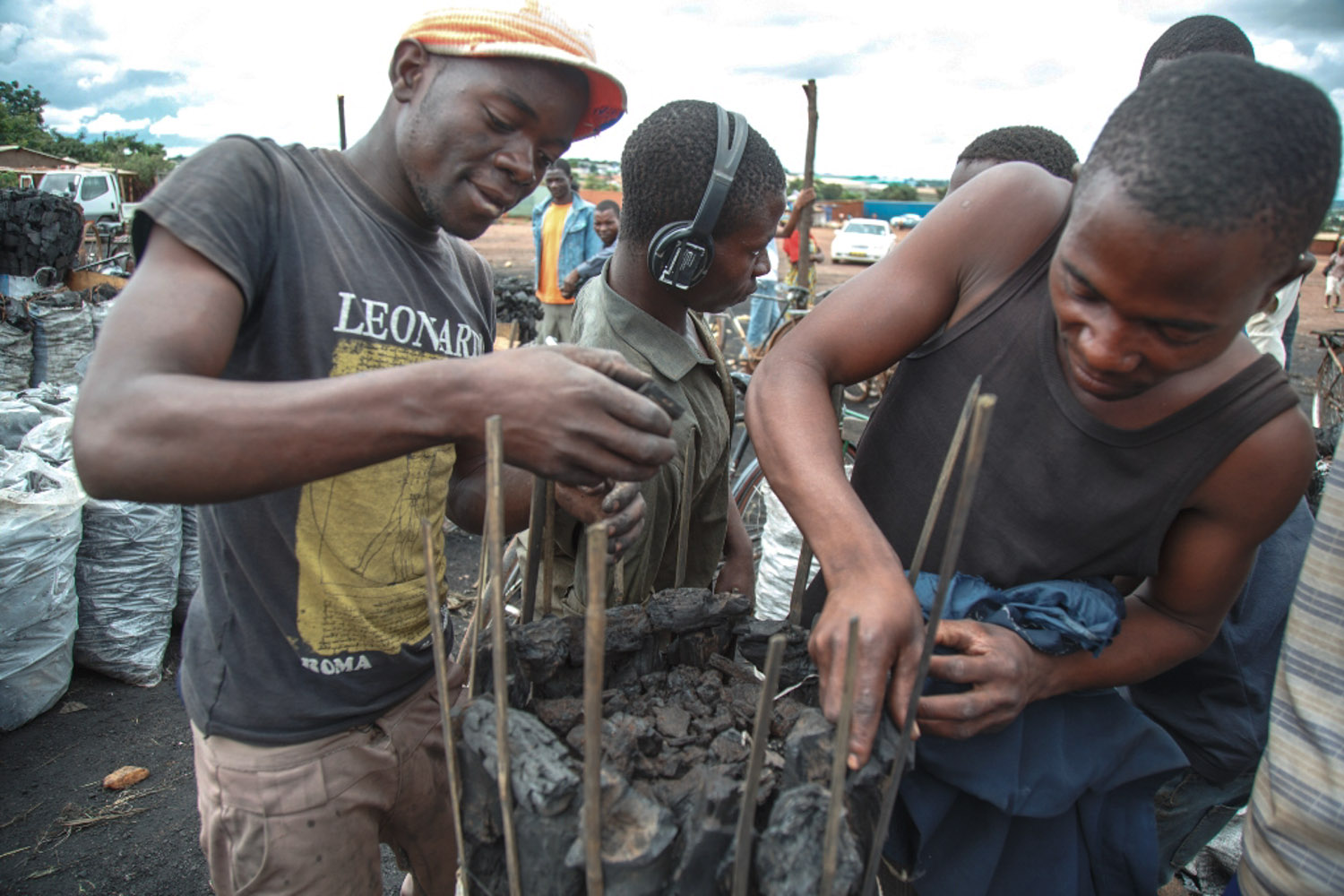 Young men packing large charcoal bags for wholesale customers.